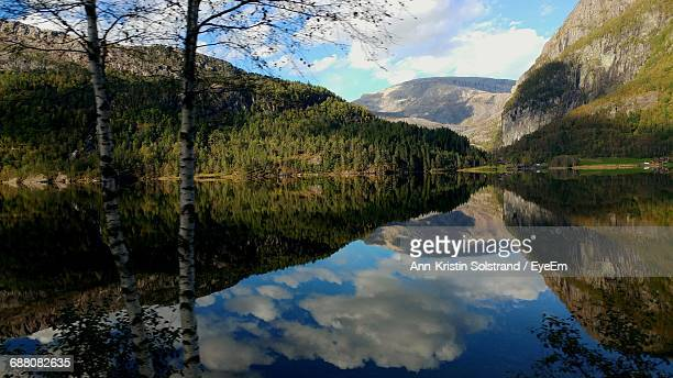 Scenic View Of Mountains Against Sky Reflecting In Calm Lake