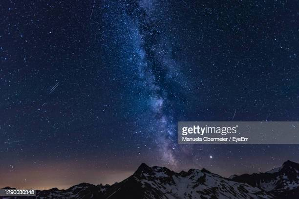 scenic view of mountains against star field at night - 冠雪 ストックフォトと画像