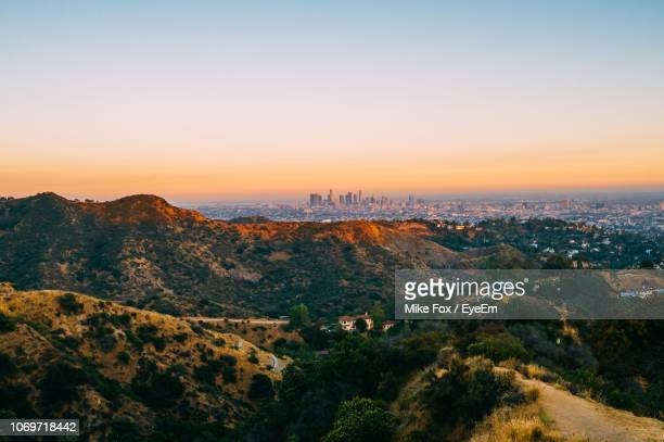 scenic view of mountains and buildings against sky during sunset - los angeles photos et images de collection