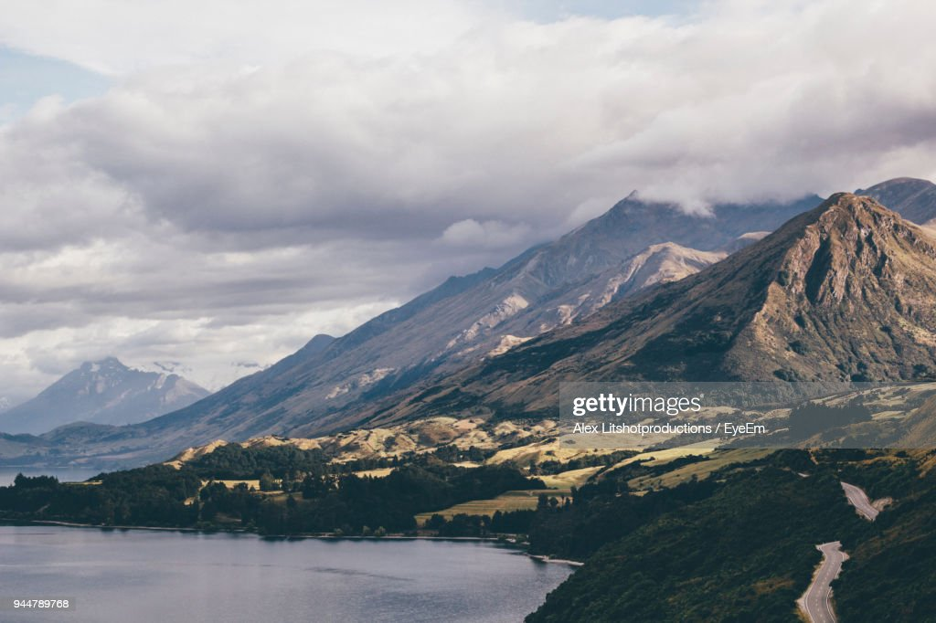 Scenic View Of Mountains And Lake Against Cloudy Sky : Stock Photo