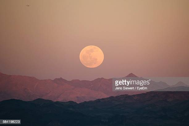 Scenic View Of Mountains And Moon At Dusk