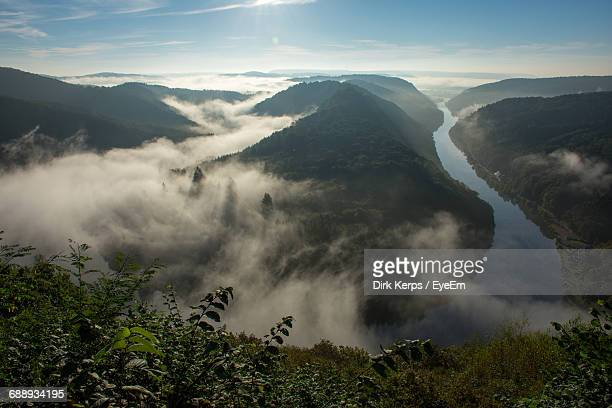 Scenic View Of Mountains And River In The Clouds Against Sky