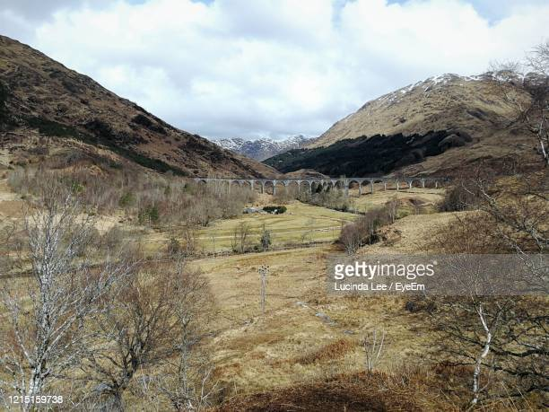 scenic view of mountains at glenfinnan viaduct against sky - lucinda lee stock pictures, royalty-free photos & images