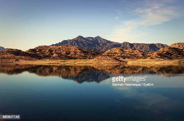 Scenic View Of Mountains By River Against Sky At Potrerillos