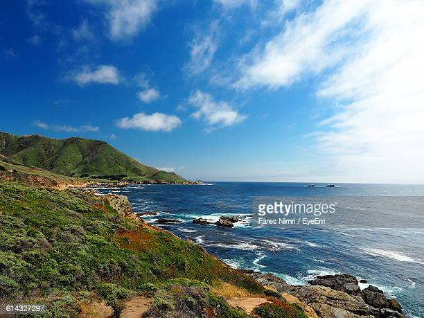 Scenic View Of Mountains By Sea Against Blue Sky