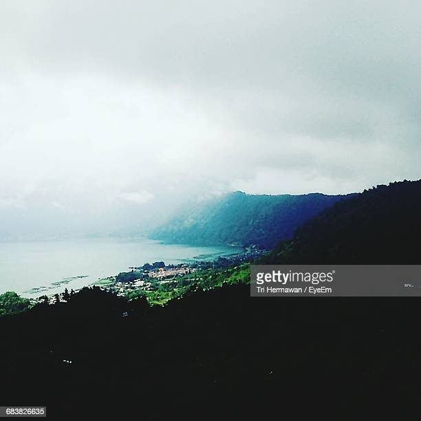 scenic view of mountains by sea against cloudy sky - kintamani district stock pictures, royalty-free photos & images