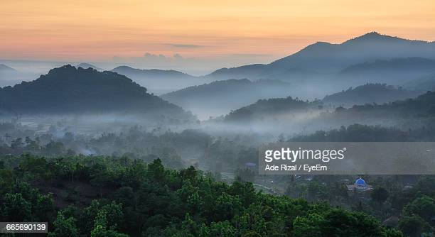 scenic view of mountains during foggy weather at sunset - ade rizal stock photos and pictures