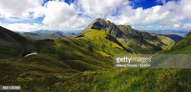 Scenic View Of Mountains In Scotland Against Cloudy Sky