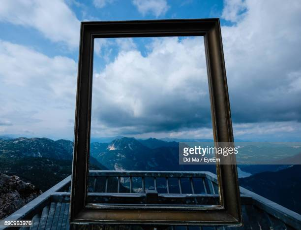 Scenic View Of Mountains Seen Through Frame Against Cloudy Sky