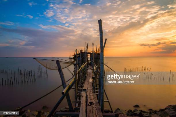 Scenic View Of Old Jetty On Lake Against Sky
