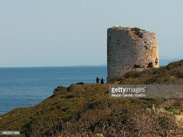 Scenic View Of Old Structure On Cliff By Sea Against Clear Sky