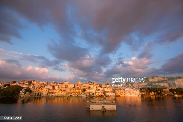 Scenic view of old town of Udaipur against cloudy sky at sunset