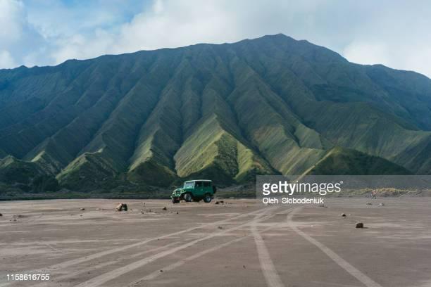schilderachtig uitzicht op ouderwetse suv rijden door de woestijn in de buurt van bromo vulkaan - internationaal monument stockfoto's en -beelden