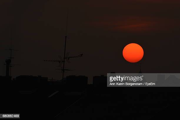 Scenic View Of Orange Sun Above Silhouette Buildings During Sunset