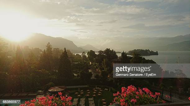 Scenic View Of Park By Lake Against Cloudy Sky At Stresa