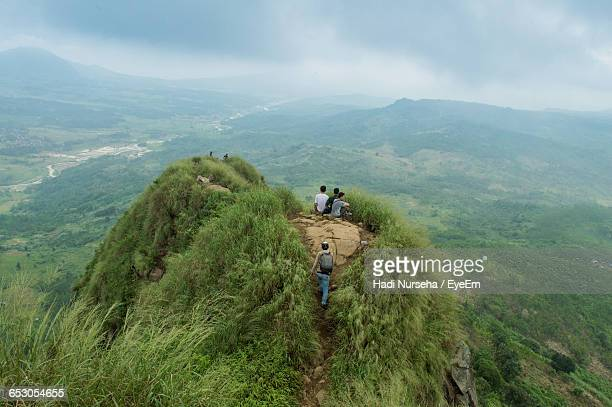 scenic view of people on a mountain overlooking green landscape against sky - bogor stock pictures, royalty-free photos & images