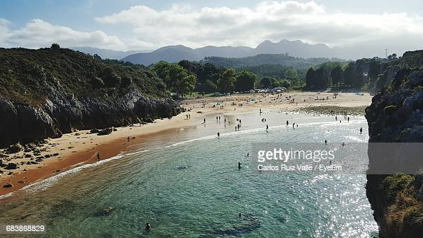 scenic view of people on beach - llanes fotografías e imágenes de stock