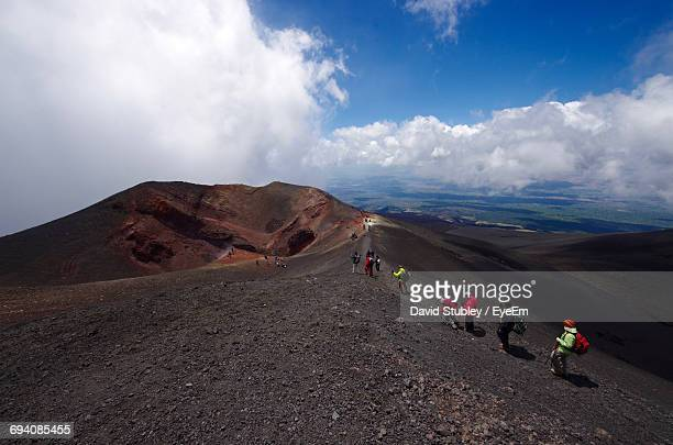scenic view of people on volcanic landscape against sky - mt etna stock pictures, royalty-free photos & images