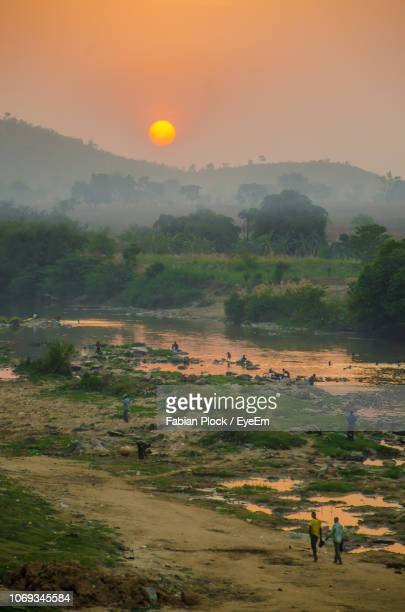 scenic view of people walking along african river during sunset, nigeria - nigeria stock pictures, royalty-free photos & images