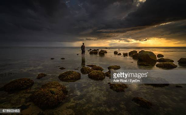 scenic view of person standing in ocean - ade rizal stock photos and pictures