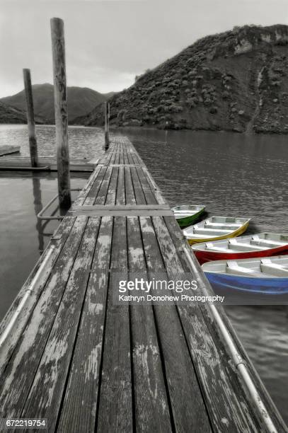 scenic view of pyramid lake with mountains, pier and boats with selective color tied up. - isolated color stock pictures, royalty-free photos & images
