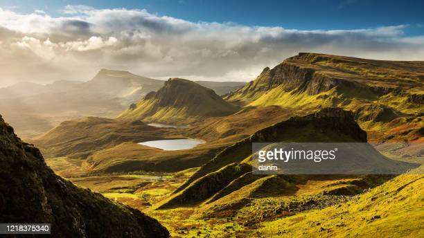 scenic view of quiraing mountains in isle of skye, scottish highlands, united kingdom. sunrise time with colourful an rayini clouds in background - scotland imagens e fotografias de stock