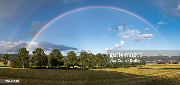 scenic view of rainbow above landscape - rainbow sky stock pictures, royalty-free photos & images