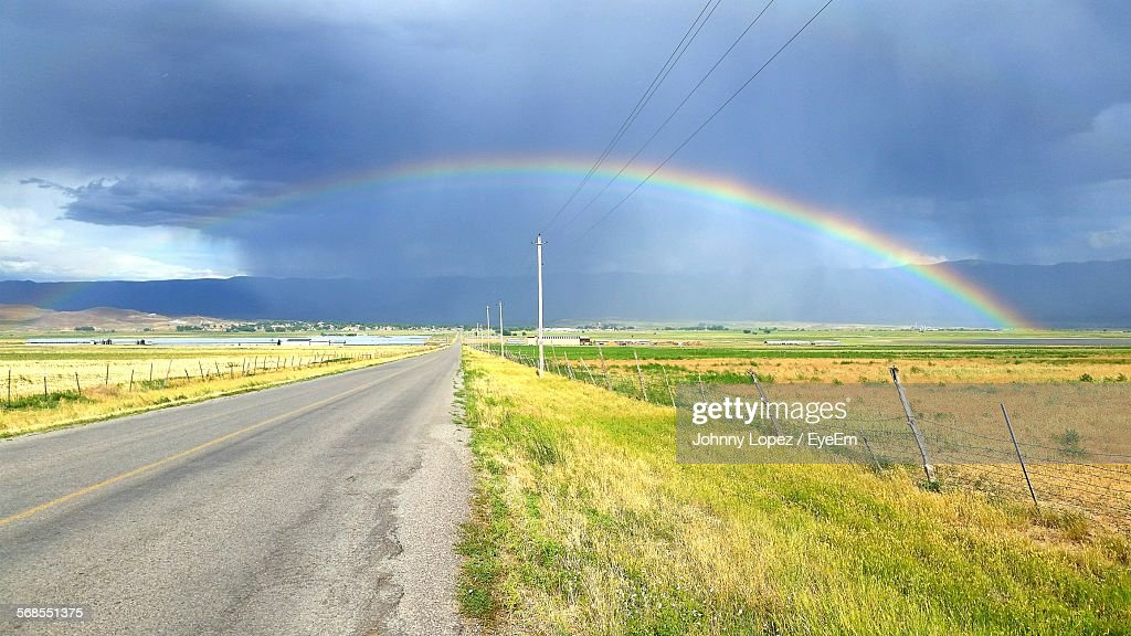 Scenic View Of Rainbow Over Grassy Fields Against Sky : Stock Photo