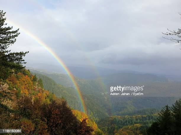 scenic view of rainbow over mountain against sky - ガール県 ストックフォトと画像