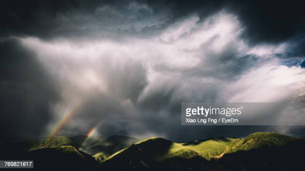 scenic view of rainbow over mountains against cloudy sky - rainbow mountains china stock-fotos und bilder