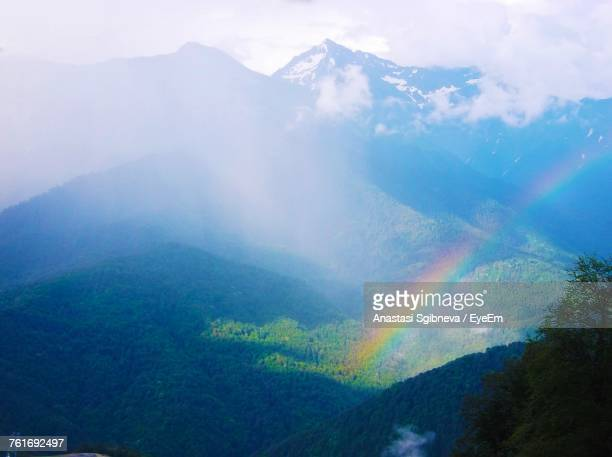 scenic view of rainbow over mountains against sky - anastasi foto e immagini stock