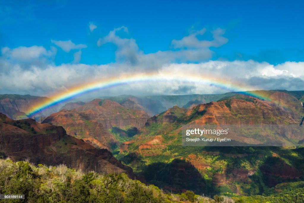 Scenic View Of Rainbow Over Mountains Against Sky : Stock Photo