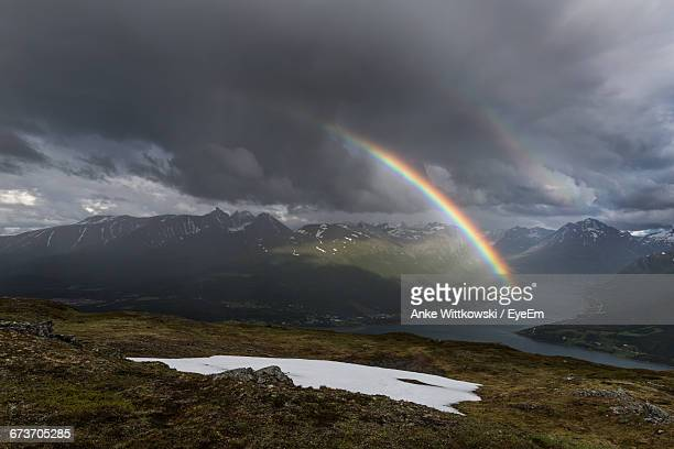 scenic view of rainbow over mountains during stormy weather - rainbow sky stock pictures, royalty-free photos & images