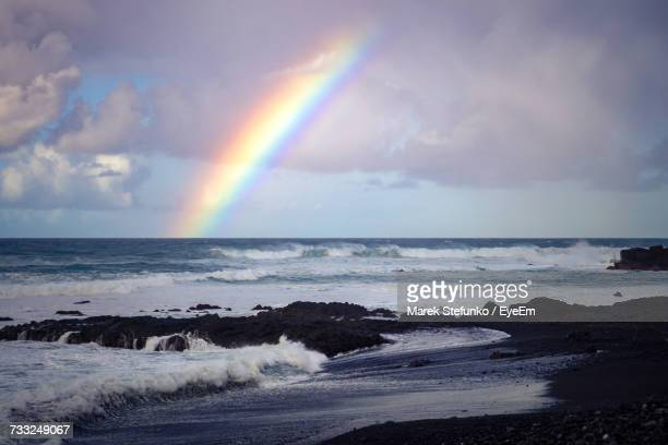 scenic view of rainbow over sea against sky - marek stefunko stockfoto's en -beelden