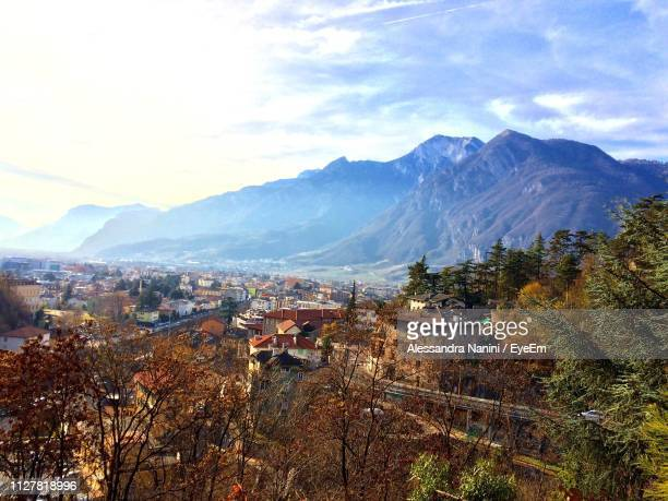 scenic view of residential district and mountains against sky - trento foto e immagini stock