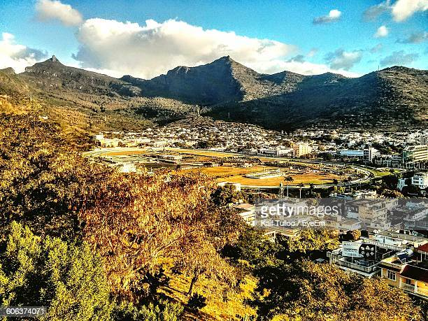 scenic view of residential district by mountains against sky - port louis stock photos and pictures