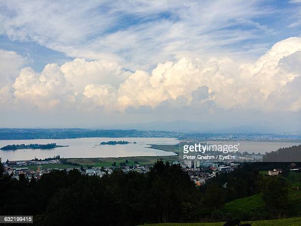 Scenic View Of Residential District By River Against Cloudy Sky