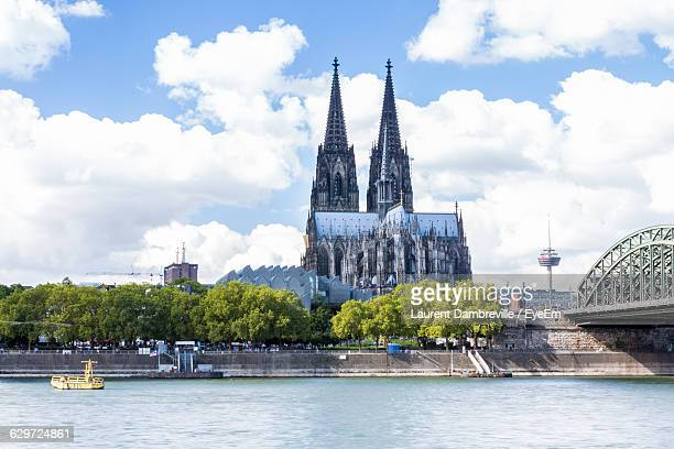 scenic view of rhine river by cologne cathedral in city against sky - cologne stock pictures, royalty-free photos & images