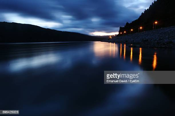Scenic View Of River Against Cloudy Sky At Dusk