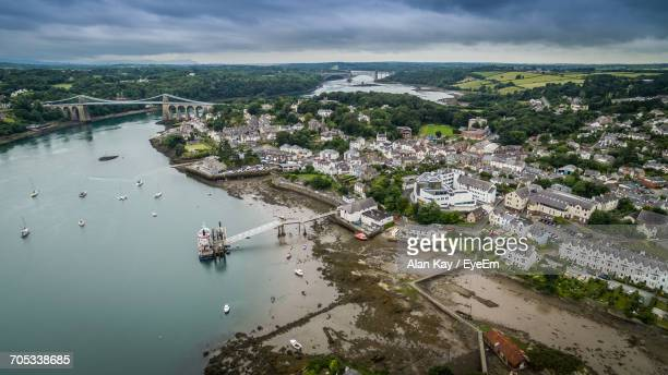 scenic view of river against cloudy sky - menai bridge stock photos and pictures