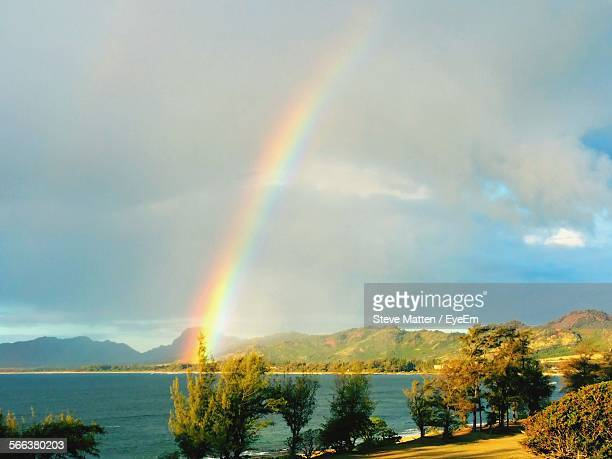 scenic view of river against rainbow in sky - steve matten stock pictures, royalty-free photos & images