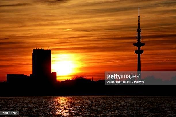 scenic view of river against silhouette heinrich-hertz-tower at sunset - hertz stock pictures, royalty-free photos & images