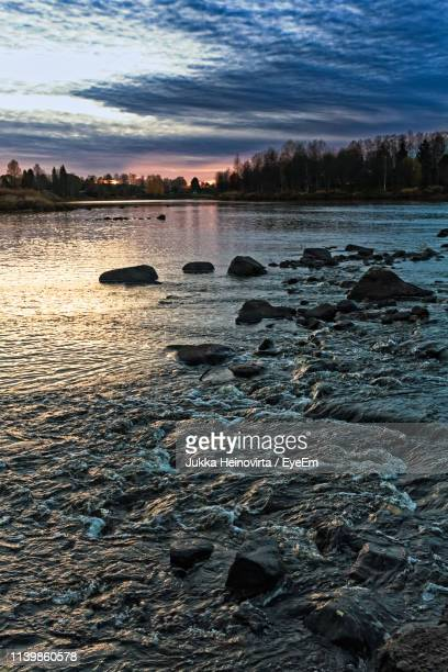 scenic view of river against sky during sunset - heinovirta stock photos and pictures