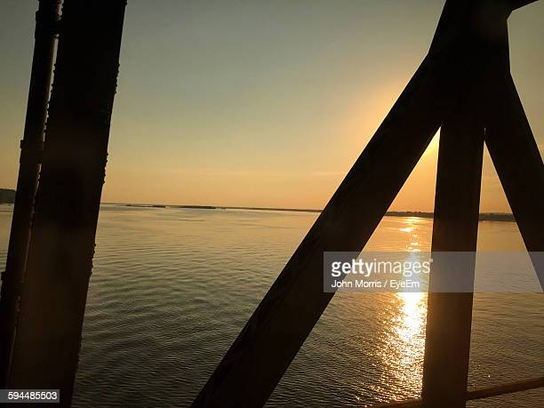 Scenic View Of River Against Sky During Sunset Seen Through Silhouette Railing