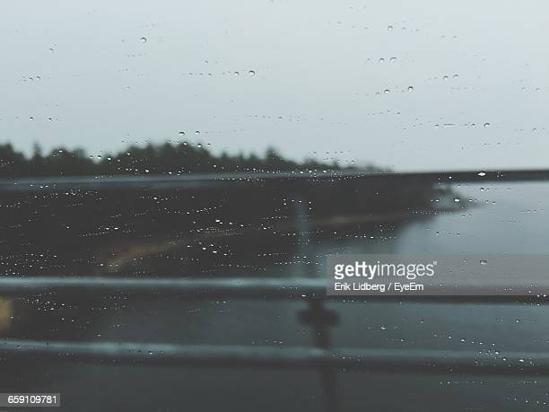 Scenic View Of River Against Sky Seen From Glass Window During Rainy Season
