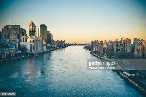 Scenic View Of River Amidst Buildings In City During Sunset