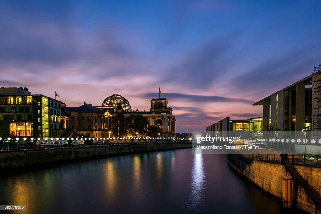 Scenic View Of River Amidst Illuminated Buildings Against Sky At Dusk : Stock-Foto