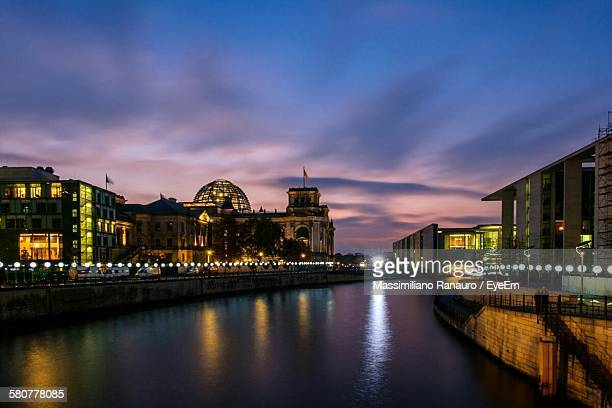 Scenic View Of River Amidst Illuminated Buildings Against Sky At Dusk