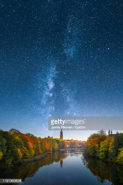 scenic view of river amidst trees against star field in sky during autumn - turku finland stock photos and pictures