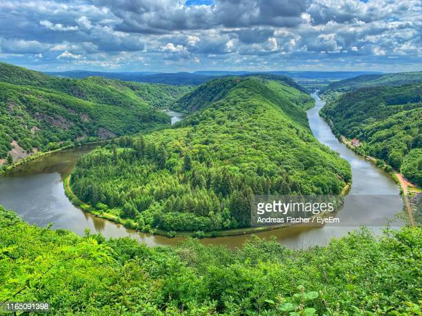 scenic view of river amidst trees and mountains against sky - moseltal stock-fotos und bilder